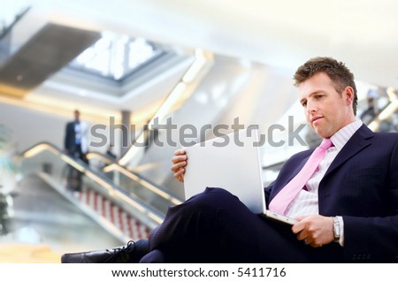 Well dressed businessman sitting in the lobby and using laptop computer.
