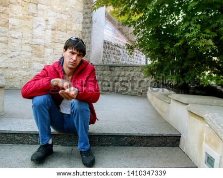 Well dressed handsome young adult man with an outstretched hand imitates begging. Sad look, hand outstretched, the guy is sitting on the steps in Heydar Aliyev Park in Kiev, Ukraine