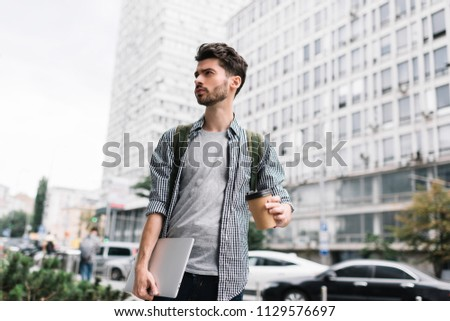 Well dressed hipster man holding laptop computer and cup of coffee, he waiting taxi. Portrait of handsome succesful businessman walking on the street and thinking about startup project.   #1129576697