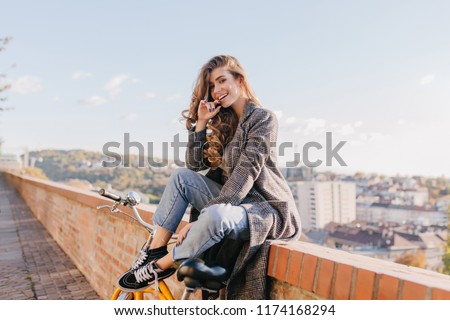 Well-dressed lady in good mood playfully posing on city background in warm weather. Charming dark-haired girl in coat sitting on the street under blue sky.
