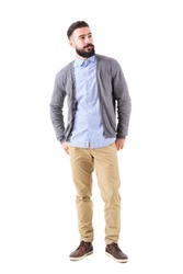 Well dressed man fashion model in gray cardigan looking up with hands in back pockets. Full body length portrait isolated on white studio background.