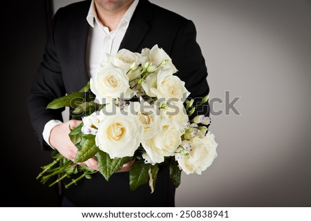well-dressed man holding a bouquet of flowers. Holidays and celebrations. Valentines day.
