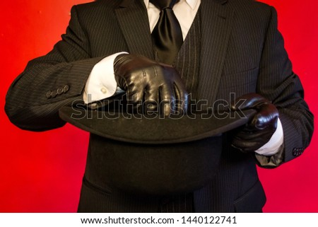 Well Dressed Man in Three-Piece Suit Reaching into a Bowler Hat While Wearing Leather Gloves