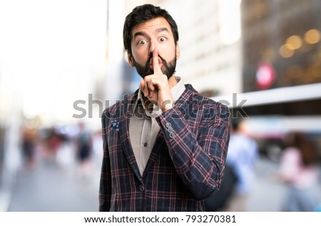 Well dressed man making silence gesture in the city #793270381