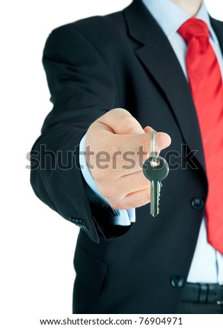 Well-dressed man offering key to Your dream ...