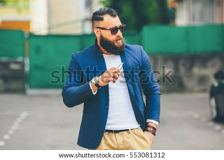 well-dressed man smoking electronic cigarette #553081312