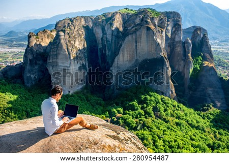Well-dressed man working with laptop sitting on the rocky mountain on beautiful scenic clif background near Meteora monasteries in Greece. Back view, general plan.