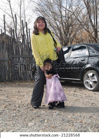 Well dressed Native American woman with a laptop standing by her car and holding her daughter's hand. In the background a traditional latilla fence.