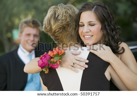 Well-dressed teenagers hugging outside