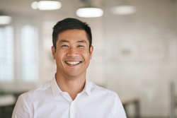 Well dressed young Asian businessman smiling confidently while standing alone in a bright modern office