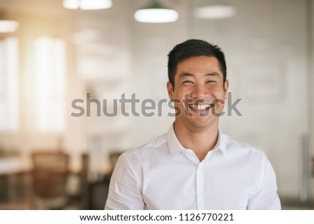 Well dressed young Asian businessman smiling while standing by himself in a bright modern office