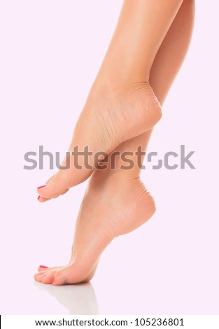 Well groomed female feet on pink background