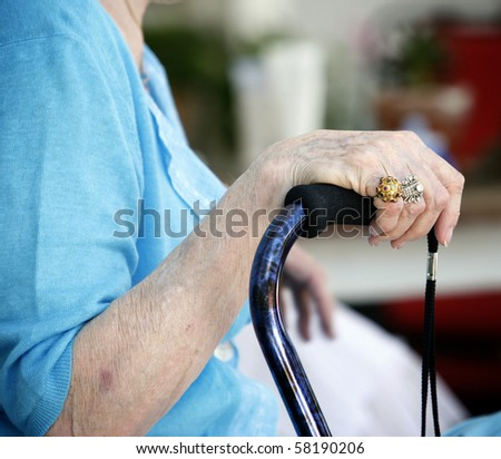 Well groomed Hand of elderly woman with beautiful rings holding walking stick