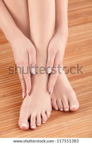 Well-groomed hands on female feet - stock photo