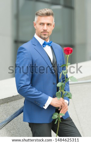 Well groomed macho tailored suit. Make good first impression. Valentines day and anniversary. Romantic gentleman. Man mature confident macho with romantic gift. Handsome guy rose flower romantic date. Foto d'archivio ©