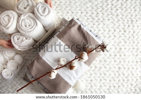 Well groomed woman hand holding a cotton branch with stack of neatly folded linens near rolled up towels in mesh basket placed on knitted chunky merino wool yarn plaid. Natural textile. Top view. Сток-фото ©