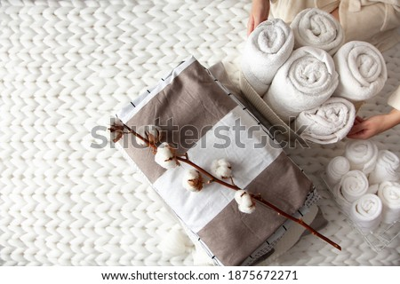 Well groomed woman hand holding a cotton branch with stack of neatly folded linens near rolled up towels in mesh basket placed on knitted chunky merino wool yarn plaid. Natural textile. Top view.