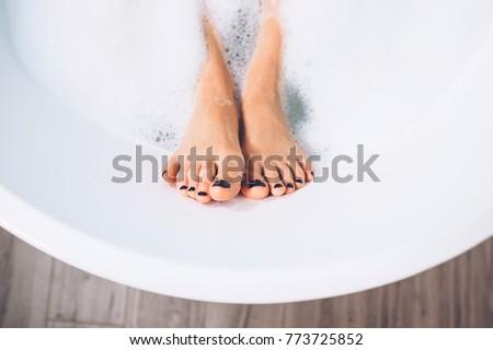 Well groomed woman's legs in bath foam close up image