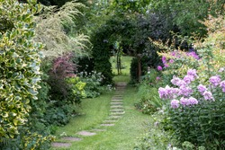 Well kept garden with lawn, stepping stones and well stocked flower beds.
