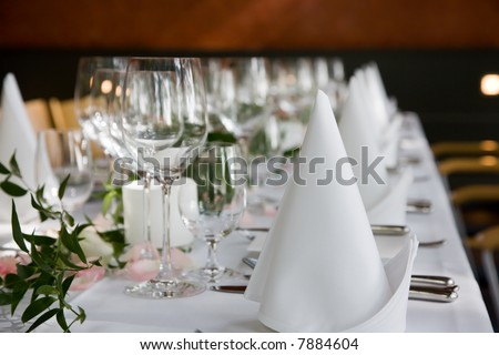Well-laid table with white folded serviettes and wine glasses.