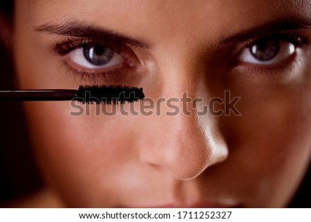 Well lit woman applying mascara to her eyelashes