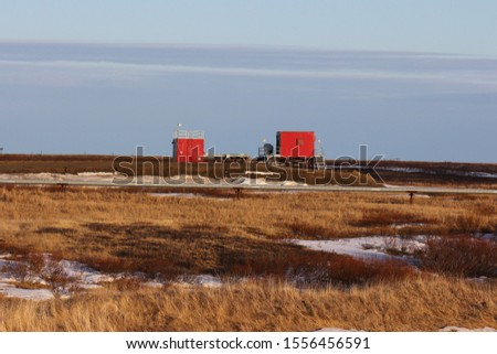 Well pad with a well house, a process module and an oil pipeline in the foreground in the oil and gas field in the Arctic tundra #1556456591