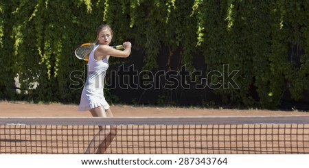 Well prepared to defend. \ Young female tennis athlete swinging racket to meet coming ball white dress miniskirt outdoor play court dark green fence background orange clay ground copy space on right