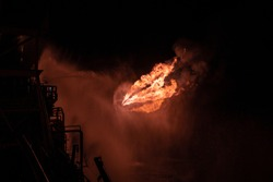 Well testing operation (flaring) of an oil and gas drilling rig. Burning huge gas flame controlled by the deluge system