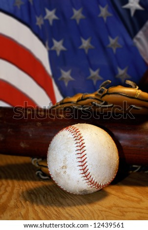 Well used baseball, bat and glove rest on a sheet of plywood with an American flag in the background.