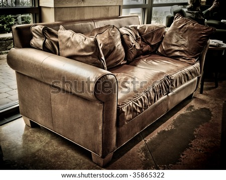 well worn and empty leather couch in a coffee shop awaiting the next