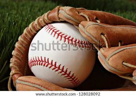 Well worn baseball glove with new ball on grass. Highly detailed closeup image taken in soft side-lighting to emphasize stitching and texture of baseball.  Shallow dof.
