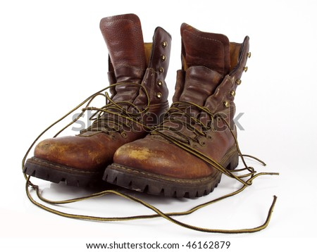 Well worn pair of leather work boots on a white background