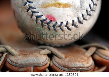 Well-worn softball in baseball glove
