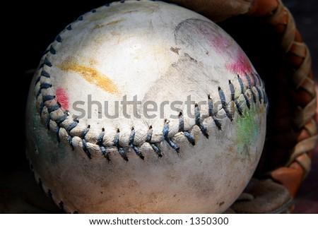 Well-worn softball in mitt