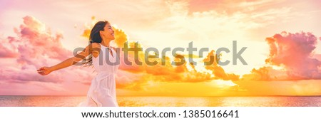 Wellbeing freedom happy woman jumping dancing of joy with open arms in the air blissful banner. Asian woman in sunset clouds pink sky background. ストックフォト ©
