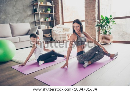 Wellbeing wellness vitality concept. Sportive active will-powered wearing sport clothes mom is sitting on the floor cute small preteen daughter repears the movements after mum #1034781634