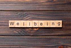 Wellbeing word written on wood block. Wellbeing text on cement table for your desing, concept.