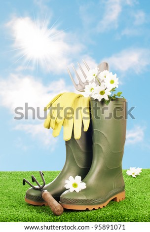 Wellington boots with garden tools on grass with blue summer sky