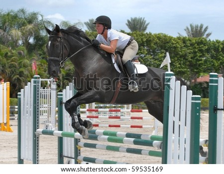 WELLINGTON, FLORIDA - AUG 21: An unidentified competitor clears a jump at the first Palm Beach County Horsemen's Association Show of the 2010-2011 season on August 21, 2010 in Wellington