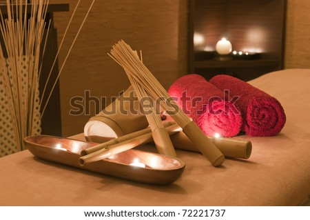 Wellness and spa concept with candles, red towels and part of massage table.