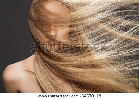 Wellness and spa. Sensual woman model with windswept flying dark blond hair on gray background. Shiny long health hairstyle. Beauty and haircare