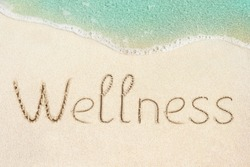 Wellness concept photo. Word Wellness handwritten on the sand. Beach and soft wave background.