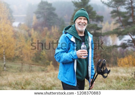 Wellness, health, activity, sports and hobby concept. Picture of happy positive mature bearded male in his seventies posing outdoors in wild nature, holding plastic bottle of water and nordic poles