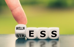 Wellness instead of stress. Hand turns a dice and changes the word