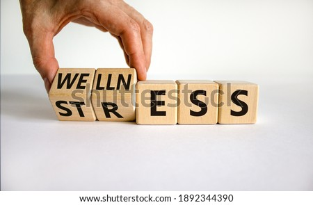 Wellness instead of stress symbol. Hand turns cubes and changes the word 'stress' to 'wellness'. Beautiful white background. Business and psychological wellness or stress concept. Copy space.