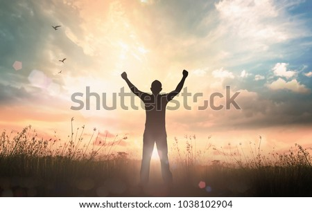 Wellness Recovery Action Plan (WRAP) concept: Silhouette of man raised hands at autumn sunset meadow background