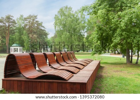 Wellness relax program center for people with wood relaxation chairs man made green park space trees blue sky background. Summer fun holiday wellness relax program tourism vacation concept - Image
