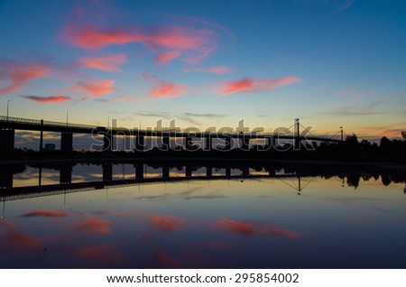 West Gate Bridge in Melbourne, Australia at dusk, with the saltwater lake of Westgate Park in the foreground.