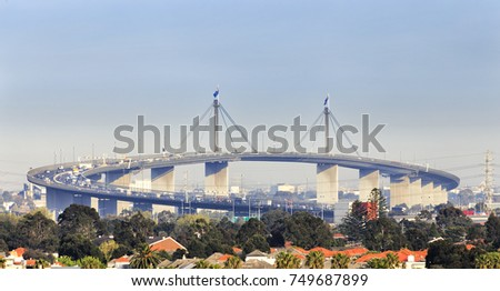 West gate multi-lane highway in Melbourne city during rush hour with traffic congestion against blue sky.