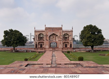 West Gate on Yumana River bank at Agra's Baby Taj mausoleum in India. Red sandstone structure decorate with white trim and figures flanked by two trees against light blue skies.
